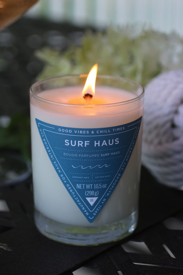 Surf Haus Coconut Wax Candle shown burning in outdoor setting.