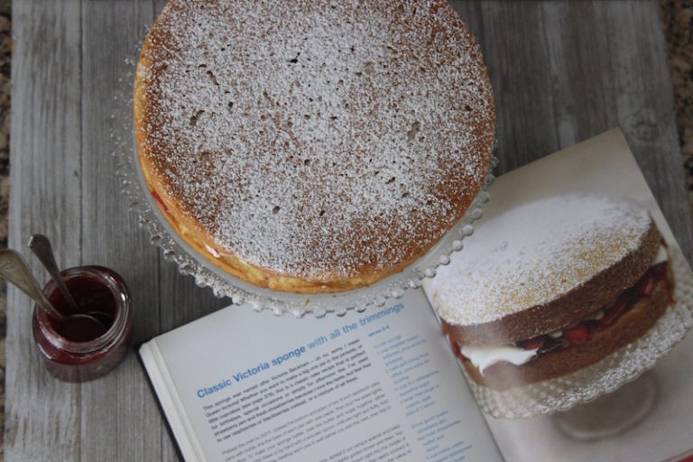 A Victoria Sponge Cake with powdered sugar and a recipe from Jamie Oliver