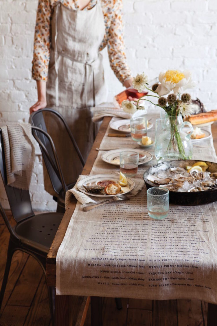Long Wooden Table with worn linen runner which includes a list of North American Oysters